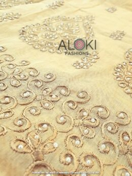Beige colored saree with all over cutwork and pearl embroidery